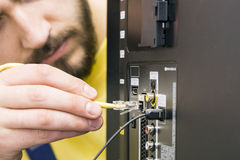 人连接互联网缆绳到电视 免版税库存图片