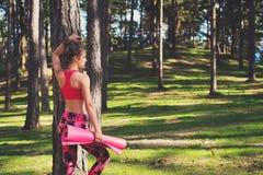 年轻人适合了佩带巧妙的手表和拿着瑜伽席子的运动妇女,准备好她的在森林身心幸福的锻炼 图库摄影