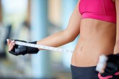 年轻人适合的妇女测量的腹部 库存照片