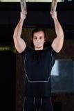 年轻人适合肌肉人画象使用体操圆环的 图库摄影