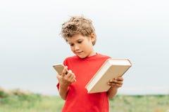 人选择在书和智能手机之间 库存照片