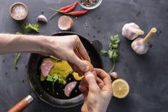 人递举行破裂的鸡蛋并且倾吐卵黄质和蛋白质在煎锅烹调它,土气样式 免版税库存照片