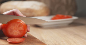 年轻人递切在切板的蕃茄 免版税图库摄影