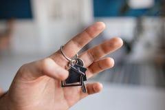 人递对负关键与房子被塑造的keychain 现代轻的大厅内部 100个票据概念美元房子做抵押 房地产,移动的家 免版税图库摄影