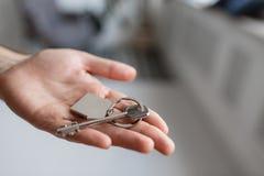 人递对负关键与房子被塑造的keychain 现代轻的大厅内部 100个票据概念美元房子做抵押 房地产,移动的家 免版税库存照片