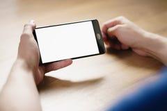 年轻人递拿着有空白的白色屏幕的智能手机 库存照片