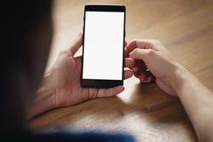 年轻人递拿着有空白的白色屏幕的智能手机 图库摄影