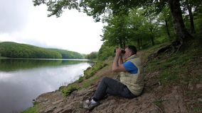 人通过双筒望远镜看在距离,当风景河岸坐在树时的阴影的绿草 股票视频