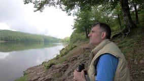 人通过双筒望远镜看在距离,当风景河岸坐在树时的阴影的绿草 股票录像