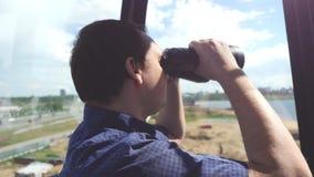 人通过双筒望远镜看,当在弗累斯大转轮时的乘驾 免版税库存图片