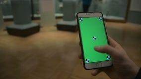 人通过在电话的一个绿色屏幕翻转有举行的在博物馆 股票视频