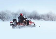 人通过随风飘飞的雪乘坐雪上电车在冬天 图库摄影