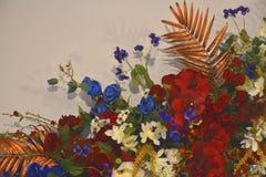 人造花混合在墙壁上装饰 免版税库存照片