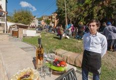 年轻人邀请品尝的Chacha的游人,传统酒精饮料 免版税库存照片