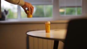 人采取一个瓶在桌上的药片 股票录像