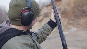人采取射击从猎枪和与一张愤怒的面孔和有效地再装猎枪单手 影视素材