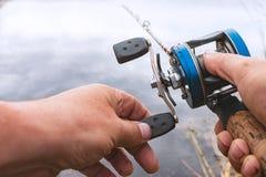 人钓鱼与一个backcasting的卷轴 库存照片