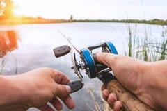 人钓鱼与一个backcasting的卷轴 免版税库存照片