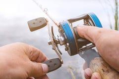 人钓鱼与一个backcasting的卷轴 库存图片