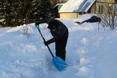 人铲起雪他的家外 免版税图库摄影