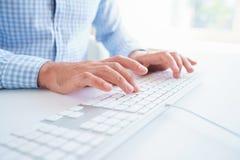 人键入在键盘的办公室工作者 库存图片
