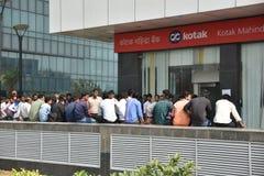 人长的队列在放置老500和1000货币笔记和得到新的货币的银行之外的 图库摄影