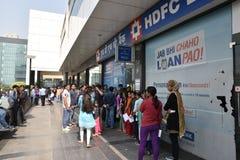 人长的队列在放置老500和1000货币笔记和得到新的货币的银行之外的 免版税图库摄影