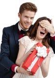 人闭上当前礼品的他的女朋友的眼睛 免版税库存照片