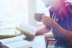 人阅读书用咖啡 免版税库存图片