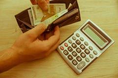 人除草现金在他的钱包外面 计数他的金钱的富人 库存图片