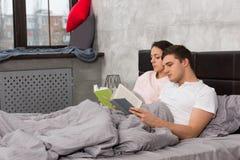 年轻人集中了夫妇阅读书,当在床a上时 免版税库存照片