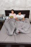 年轻人集中了对阅读书,当在床上和时 图库摄影