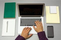 人顶视图与在家膝上型计算机一起使用在办公室或 库存照片