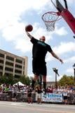 人飞跃阻塞在室外灌篮比赛的篮球 免版税库存图片