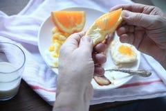 人食用与早餐的新鲜的桔子 库存图片