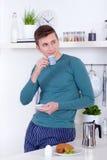 年轻人食用早餐在他的厨房 免版税库存照片