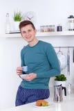 年轻人食用早餐在他的厨房 库存照片