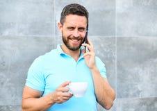 人饮料热奶咖啡讲电话灰色墙壁背景 原因企业家饮料咖啡 即使您喝咖啡  免版税图库摄影