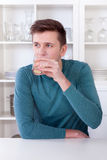 年轻人饮用的刷新的柠檬水在他的厨房里 免版税库存图片