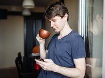 人饮用的咖啡和使用流动智能手机 库存图片