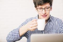人饮用的咖啡和使用膝上型计算机 免版税库存照片