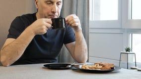 人饮用的咖啡早晨在厨房里在家 因为他有很多问题,他是非常哀伤的 股票视频