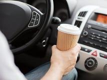 人饮用的咖啡,当驾驶汽车时 库存照片