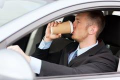 人饮用的咖啡,当驾驶汽车时 图库摄影