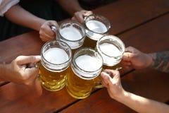 人饮用的啤酒在一个传统巴法力亚啤酒庭院里