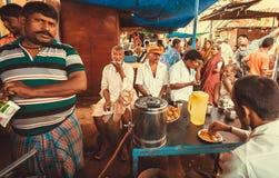 人饮用的茶和谈话在地方村庄市场室外咖啡馆  图库摄影