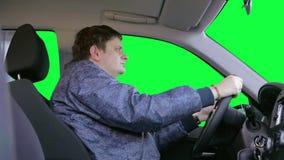 人驾驶汽车反对绿色背景 股票录像