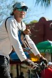 人骑有小狗的自行车被束缚对胸口 免版税库存图片
