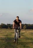 年轻人骑自行车者在木头的骑马自行车在日落 免版税库存图片