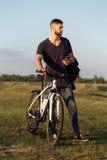 年轻人骑自行车者在木头的骑马自行车在日落 免版税图库摄影